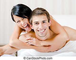 Close up of laughing couple who plays in bedroom. Woman...
