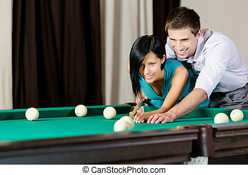 Man teaching girl to play billiards