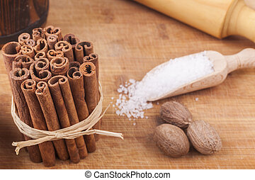 Cinnamon Pile - Baking ingredients an ustensils on brown wod...