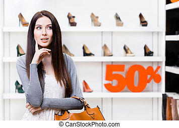 Portrait of young woman in shop with 50% sale - Portrait of...