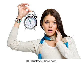 Amazed young woman with alarm clock wearing colored scarf...