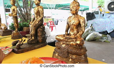 A buddha statues with gold flakes