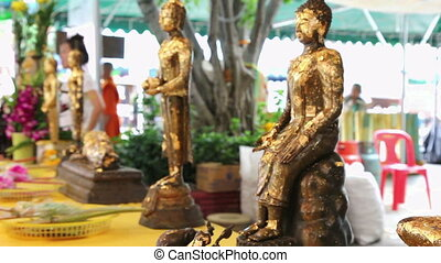 A buddha statues with gold flakes waving in the temple