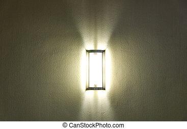 Lighting bulb on dark green wall