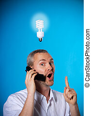 Eureka! - man wih a beard with a light bulb on the phone