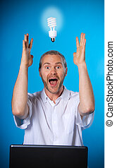Eureka! - man wih a beard with a light bulb on the laptop