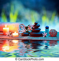 two candles and towels black stones