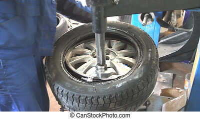 Mechanic removes car tire closeup