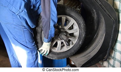 mechanic repairman making wheel balancing on the machine...