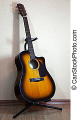 six-string acoustic guitar on a stand on light background