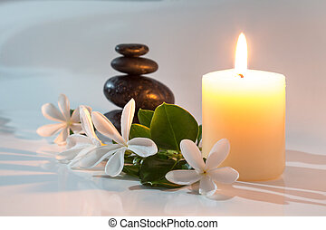 tiare flowers, candle and stones