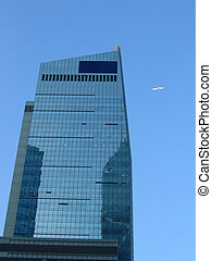 Corporate building with a plane on the blue sky, place st...