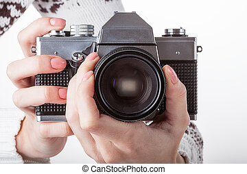 Sharpening - A hands with a reflex camera setting the...