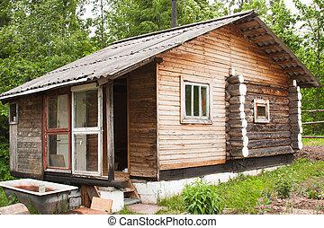 wooden bath-house on a suburban area in a garden