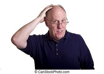 An Older Man in Blue Shirt Rubbing Bald Head - An older man...