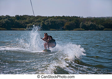 Wakeboarder - Wakeboard rider among water splashes