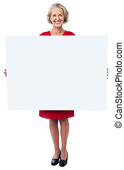 Glamorous woman holding blank ad board - Attractive aged...