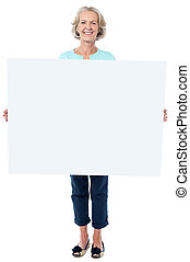 Casual old lady holding a blank billboard - Happy aged woman...