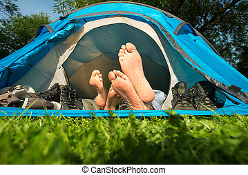 Couple on camping - Feet of a young couple lying in a tent