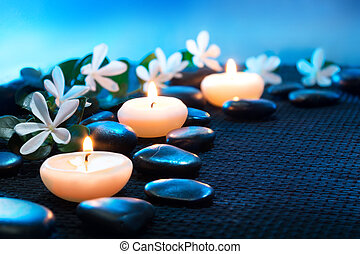 candles and black stones on black mat