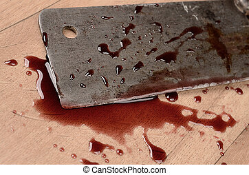 Old rusty meat cleaver with blood on a wooden floor