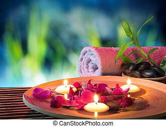 dish spa with floating candles, orchid, bambu towel in...