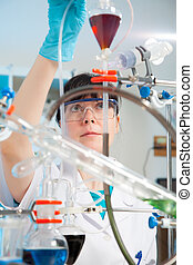 Scientific researcher holding at a liquid solution in a lab