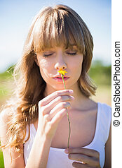 Pensive young woman smelling flower while having a walk on...