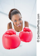 High angle view of cheerful fit woman with red boxing gloves...