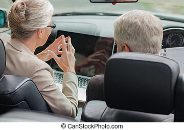 Business people working together on laptop in cabriolet on a...