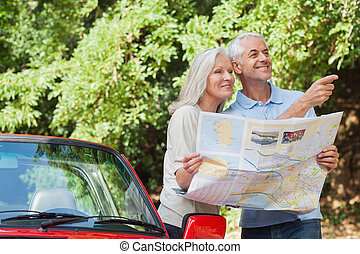 Cheerful mature couple reading map looking for direction -...