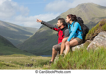 Couple taking a break after hiking uphill with man pointing...