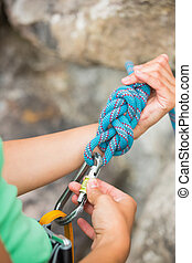 Female rock climber adjusting her harness by the rock face