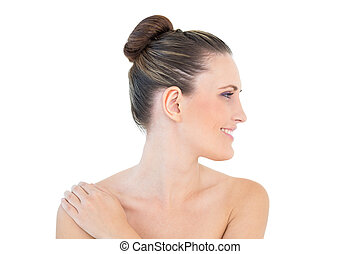 Smiling woman looking aside with hand on shoulder against...