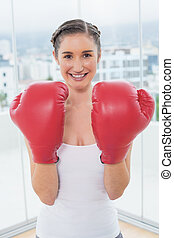 Cheerful sporty brunette wearing boxing gloves in bright...