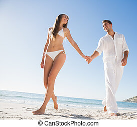 Beautiful blonde holding hands with happy boyfriend on the...