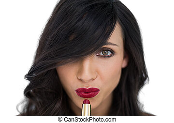 Sexy brunette applying red lipstick on white background