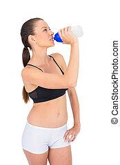 Toned woman in sportswear drinking water