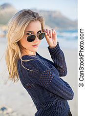 Attractive casual blonde looking over her sunglasses -...