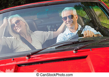 Happy mature couple in red cabriolet going for a ride on...