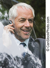 Happy mature businessman on the phone driving expensive car