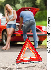 Close up on triangle warning sign with broken down car on...