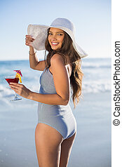 Gorgeous woman in swimsuit on a sunny day holding cocktail looking over shoulder