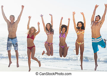 Group of friends having fun on the beach against the sea on...