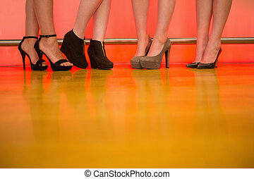 Womens legs wearing high heels at a bar of nightclub