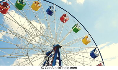 Underside view of a ferris wheel over blue sky