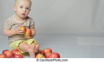 baby playing with apples