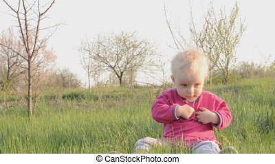 Baby sits on a grass, dolly shot