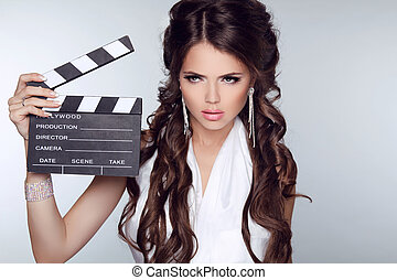 Beautiful brunette woman holding Clapper Board against a...