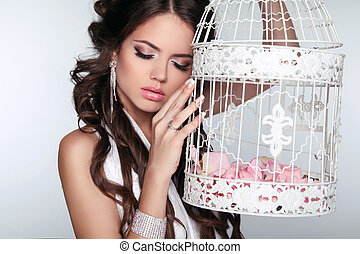 Tender Woman holding vintage bird cage isolated on grey...